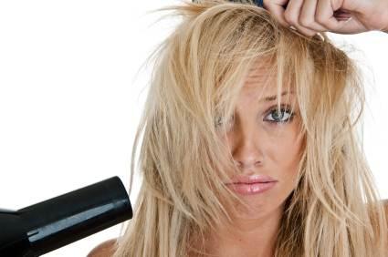 Frau mit zersaustem Haar und Fön