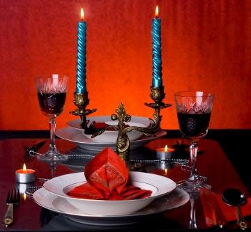 Gedeckter Tisch mit Kerzen, Tellern und gefüllten Rotweingläsern - (Foto: iStockphoto/Zeljko Santrac)