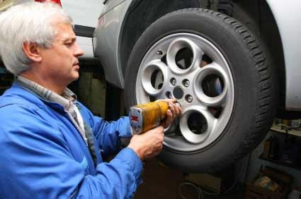 Mann wechselt Reifen in einer Werkstatt - (Foto: iStockphoto/bojan fatur)