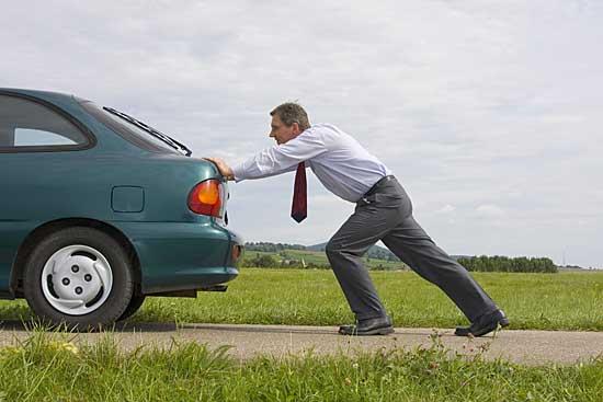Mann schiebt Auto an