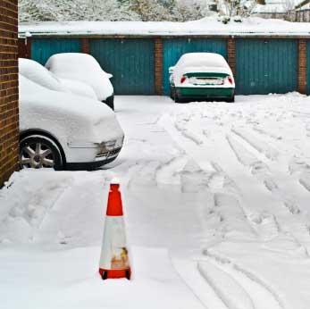 Verschneite Autos vor Garagen