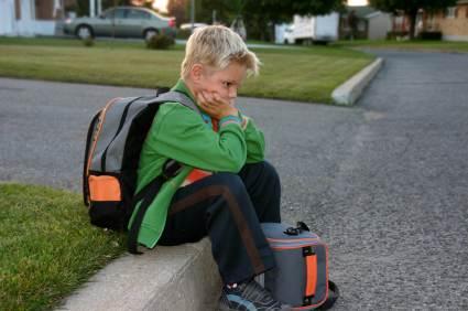 Schulkind sitzt auf dem Gehsteig und wartet auf den Schulbus - (Foto: iStockphoto/Ju-Lee)