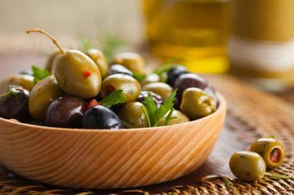Eingelegte Oliven in einer Holzschale - (Foto: iStockphoto/Vitalina Rybakova)